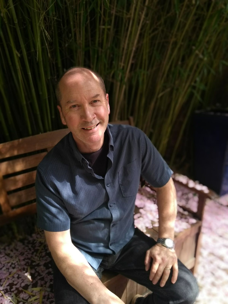 Photo image of historian Stephen Brumwell sitting on a garden bench, smiling.