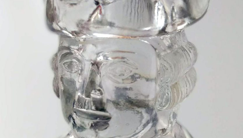 Photo image detail of a glass decanter shaped like George Washington, focusing on the head.